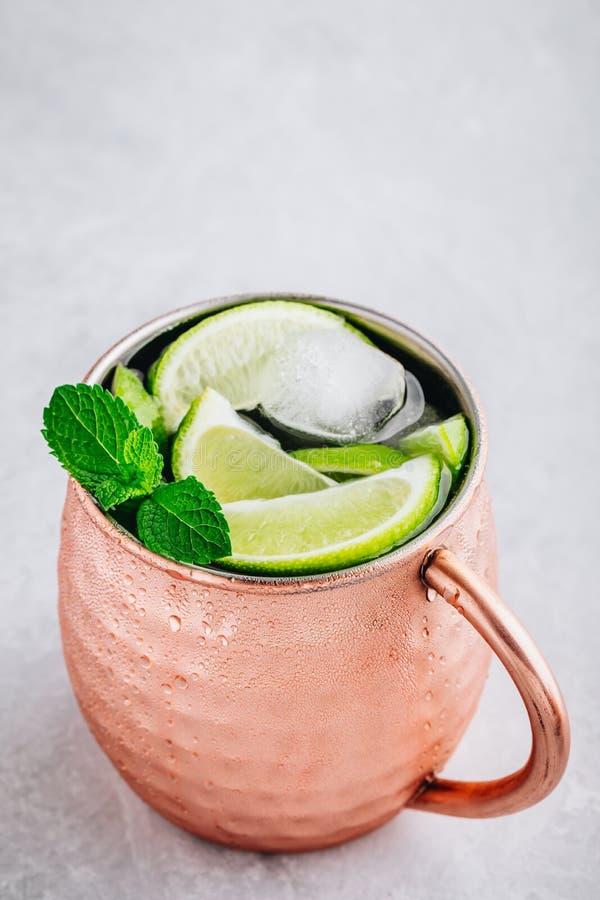 Cocktail ghiacciato del mulo di Mosca in tazza di rame con calce ed e la menta su fondo di pietra grigio fotografie stock