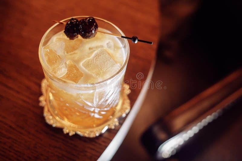 Cocktail giallo ricco con ghiaccio e la ciliegia su un bastone immagini stock libere da diritti