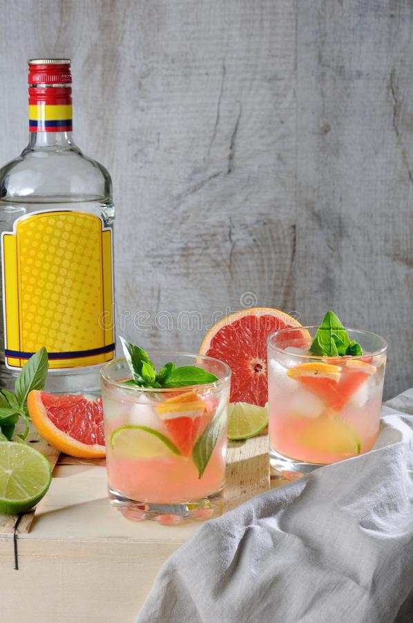 Cocktail of gin and grapefruit. Cocktail from London dry gin with juice from squeezed red grapefruit and leaves of delicate basil of lemon, lime slices and royalty free stock photo