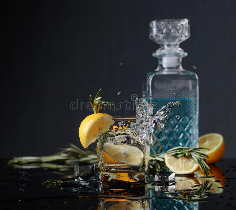 Cocktail gin-tonic with lemon slices and twigs of rosemary. Lemon slice falls into the glass. Copy space royalty free stock image