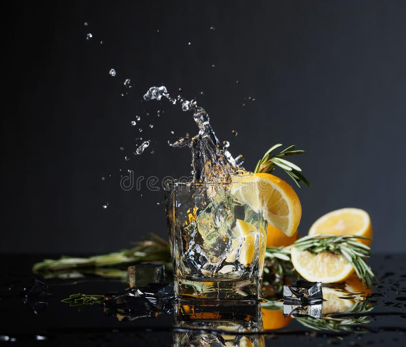 Cocktail gin-tonic with lemon slices and twigs of rosemary. Lemon slice falls into the glass. Copy space royalty free stock photo