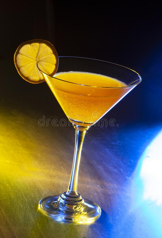 Cocktail of gin and tonic soda garnished by lemon slice on bar with blurry restaurant bar Low angle close up royalty free stock images