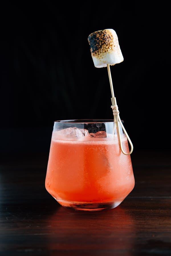 Cocktail glacé rouge avec la guimauve brûlée dans le verre à boire sur la table en bois avec le fond noir photo libre de droits
