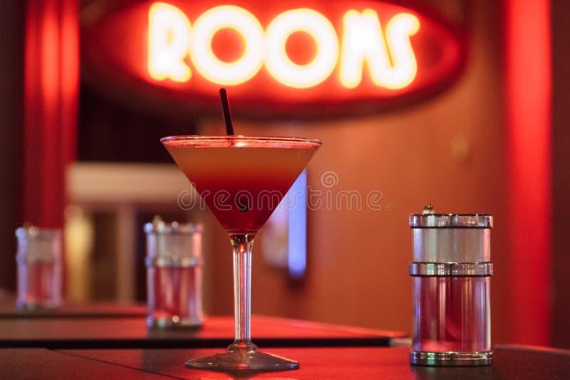 Cocktail-Glas u. Stroh mit opulentem Neonlicht stockfotografie