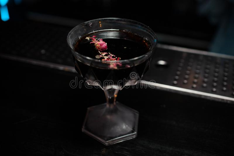 Cocktail glass with alcoholic drink decorated with rose petals royalty free stock image