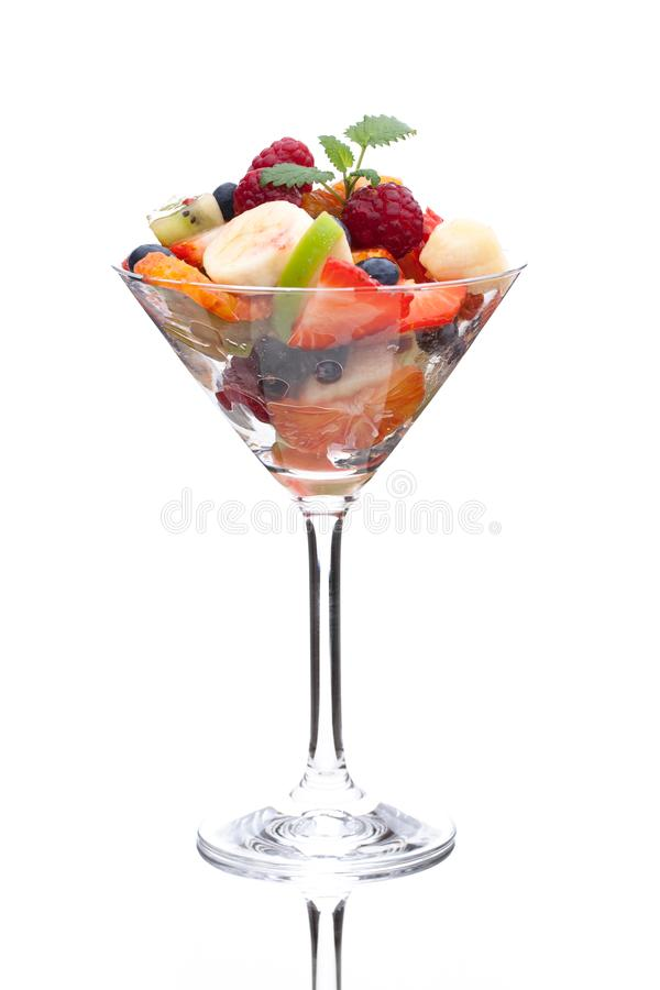 A cocktail glass filled with sorted fruits stock image