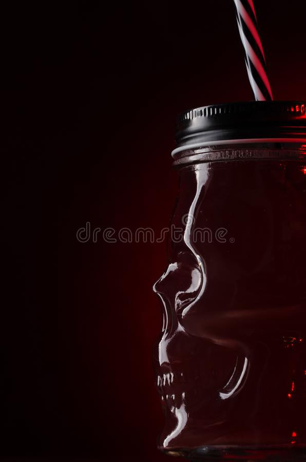 Cocktail in glass in the form of a skull on red light background. Bar, halloween, party, alcohol, drink, black, decoration, fresh, alcoholic, cold, rum, spooky stock photos