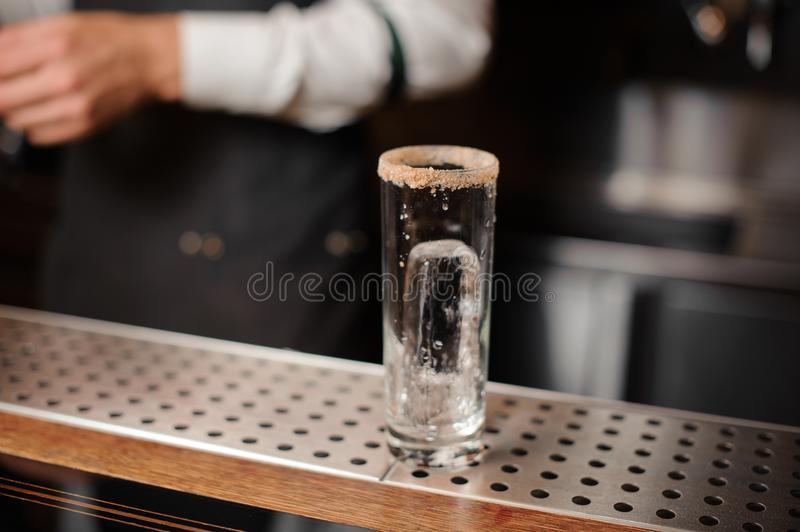 Cocktail glass with an ice cube and sugar edge on the bar counter stock images