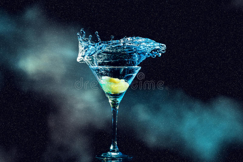 Cocktail in glass with splashes. And lemon on dark smoky background. Party club entertainment stock images