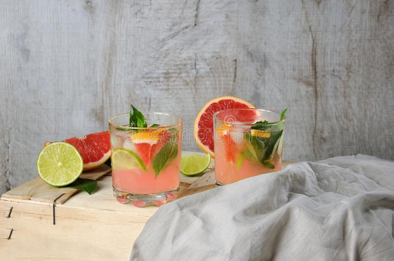 Cocktail of grapefruit and lemon basil. Cocktail of juice squeezed red grapefruit and leaves of delicate lemon basil, lime slices and chilled ice cubes stock photos