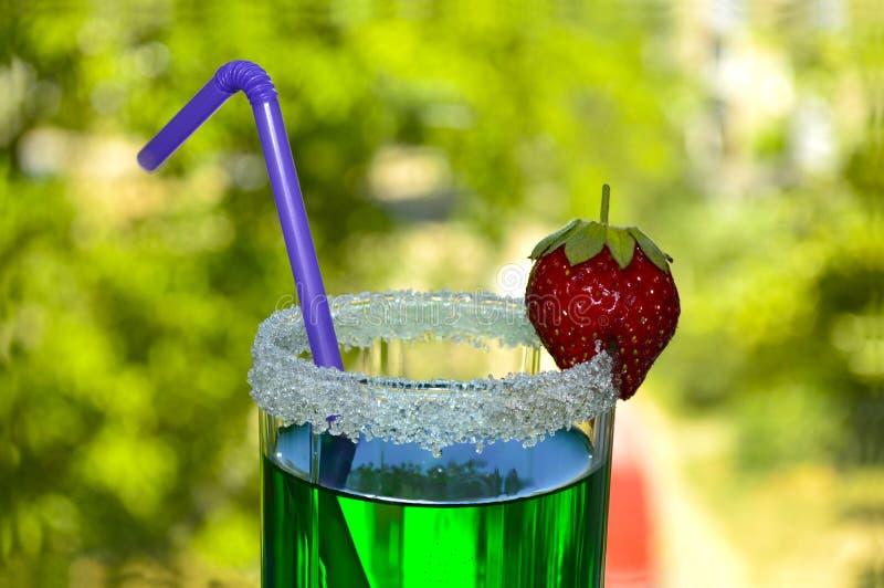 Cocktail heldergroen met aardbeien en stro stock afbeeldingen
