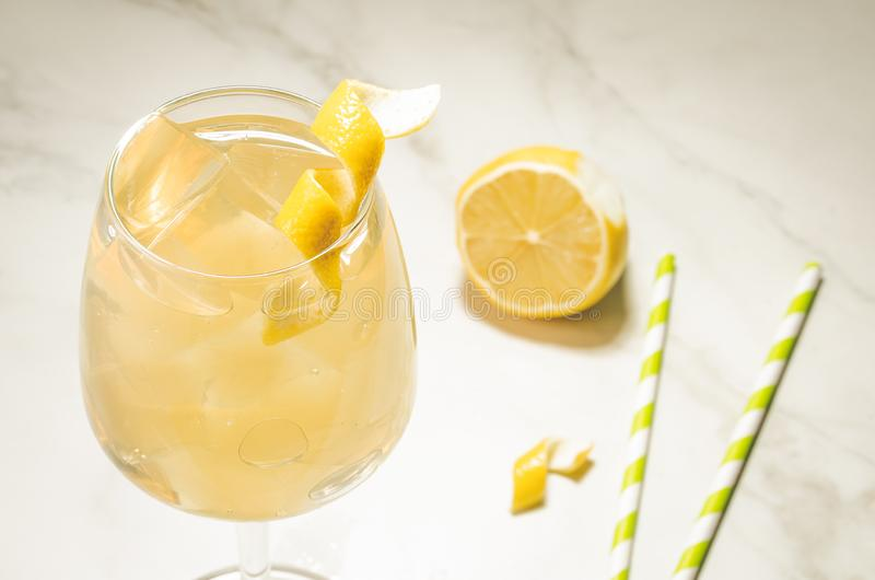 cocktail with ice and a lemon/cocktail with ice, straws and a lemon on a white table. Selective focus stock image