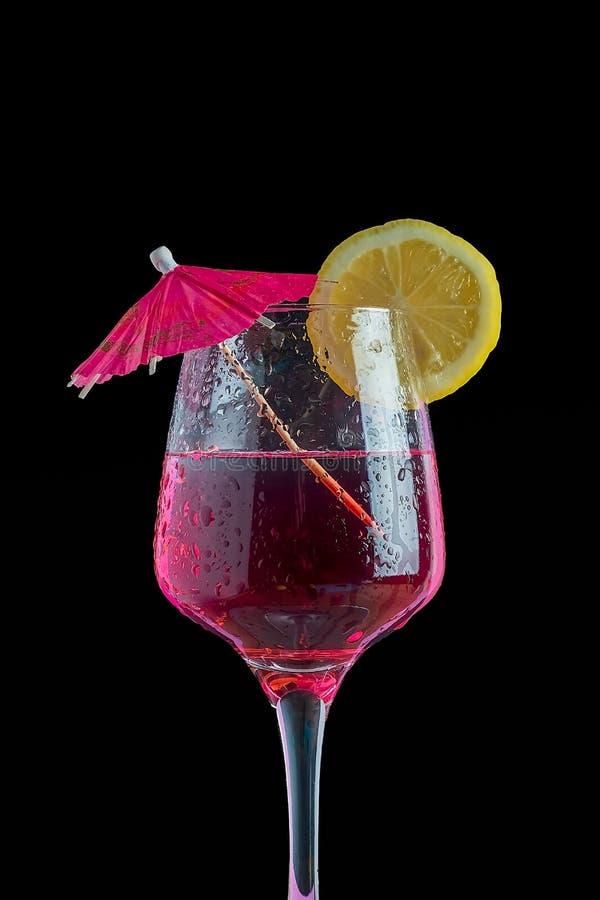 Cocktail isolato nel fondo nero con la fetta e l'ombrello del limone fotografie stock