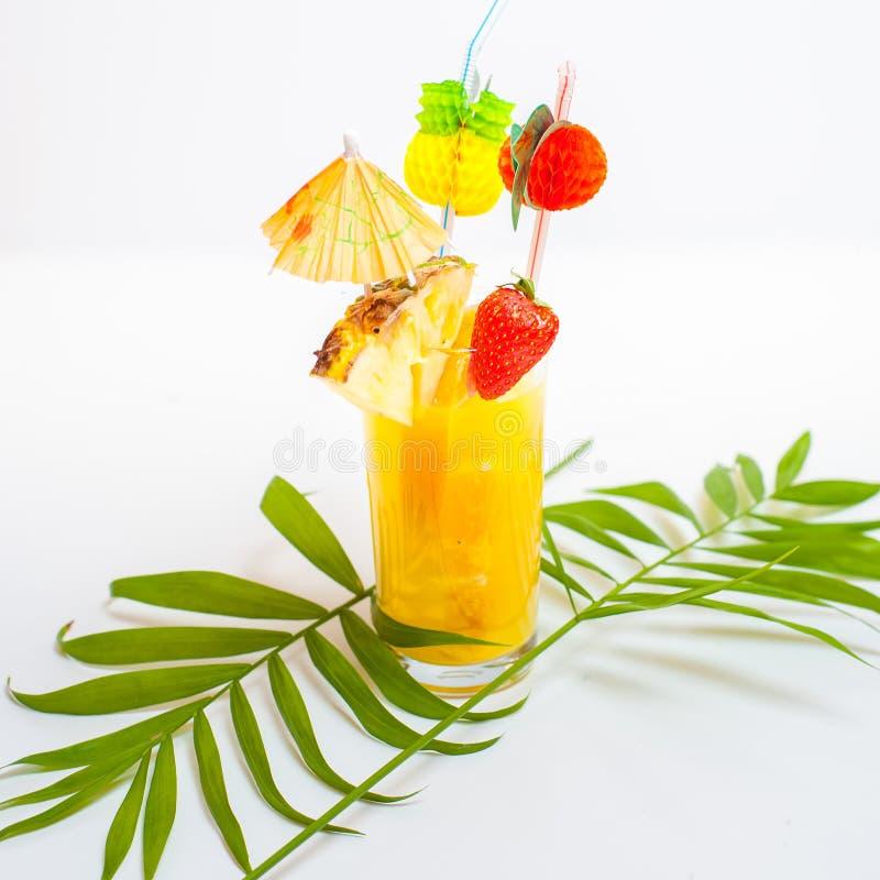 Cocktail jaune coloré d'été décoré des fruits tropicaux, photo libre de droits