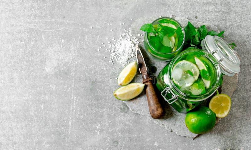 Cocktail in kruik - muntbladeren, ijs, rum en kalk op een steenbasis met een mes voor citrusvrucht en suiker stock foto's