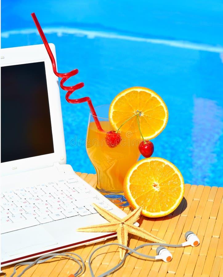 Cocktail, Laptop und Starfish auf Poolhintergrund stockfotografie