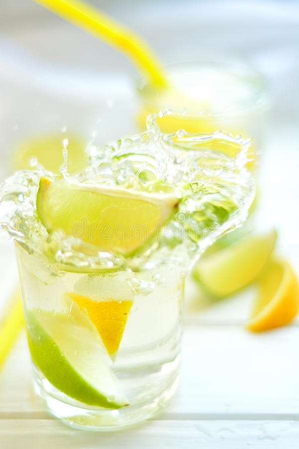 Cocktail lemon and lime in a glass with water splashes stock images