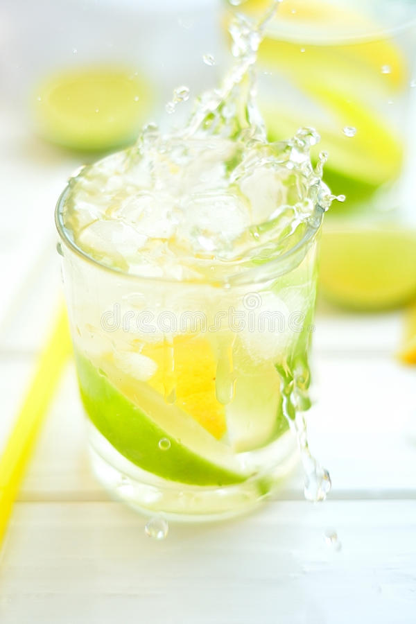 Cocktail lemon and lime in a glass with water splashes stock image