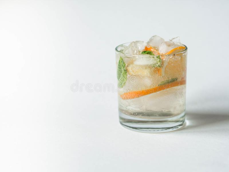 Cocktail or lemonade with mint and orange in glass. Fruit lemonade. White background. Healthy citrus summer drink stock image