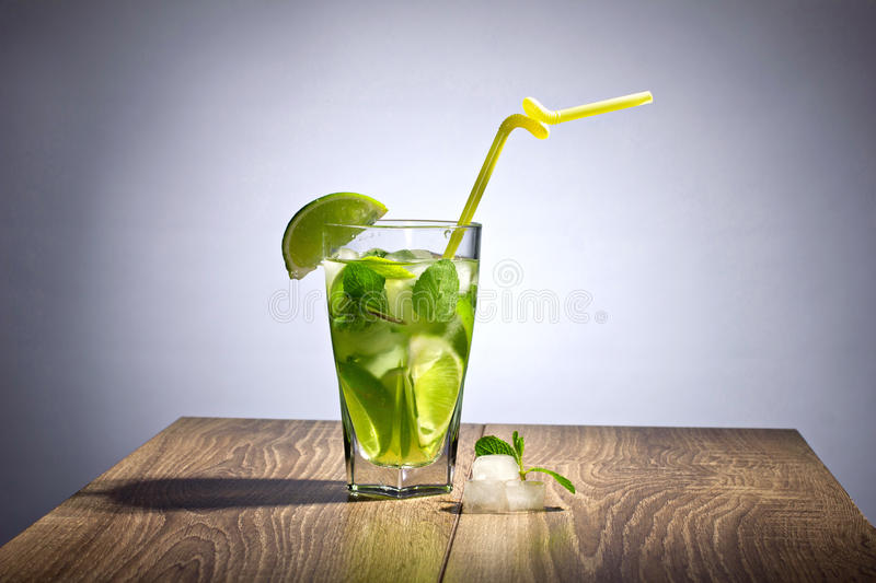 Cocktail with lime. And mint on wooden table on gray background stock images