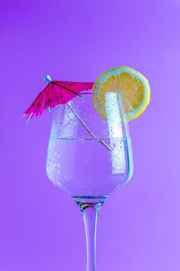 Cocktail lokalisiert im purpurroten Hintergrund mit Zitronenscheibe und -regenschirm stockfotos