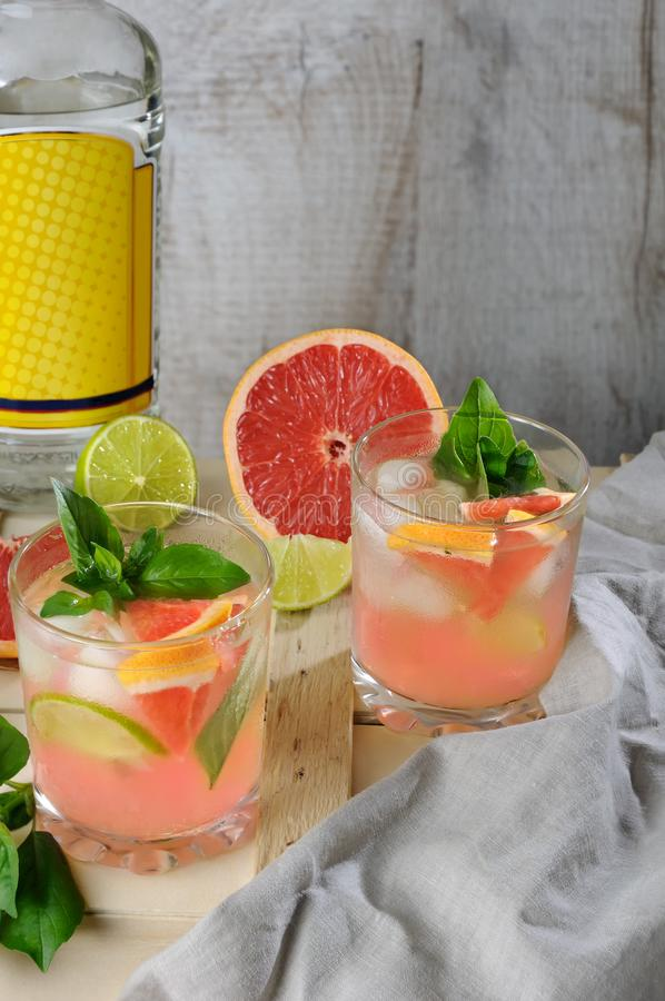 Cocktail of gin and grapefruit. Cocktail from London dry gin with juice from squeezed red grapefruit and leaves of delicate basil of lemon, lime slices and royalty free stock image