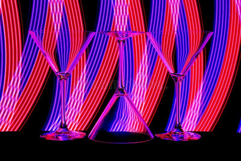 Cocktail / martini glasses with neon light behind royalty free stock images