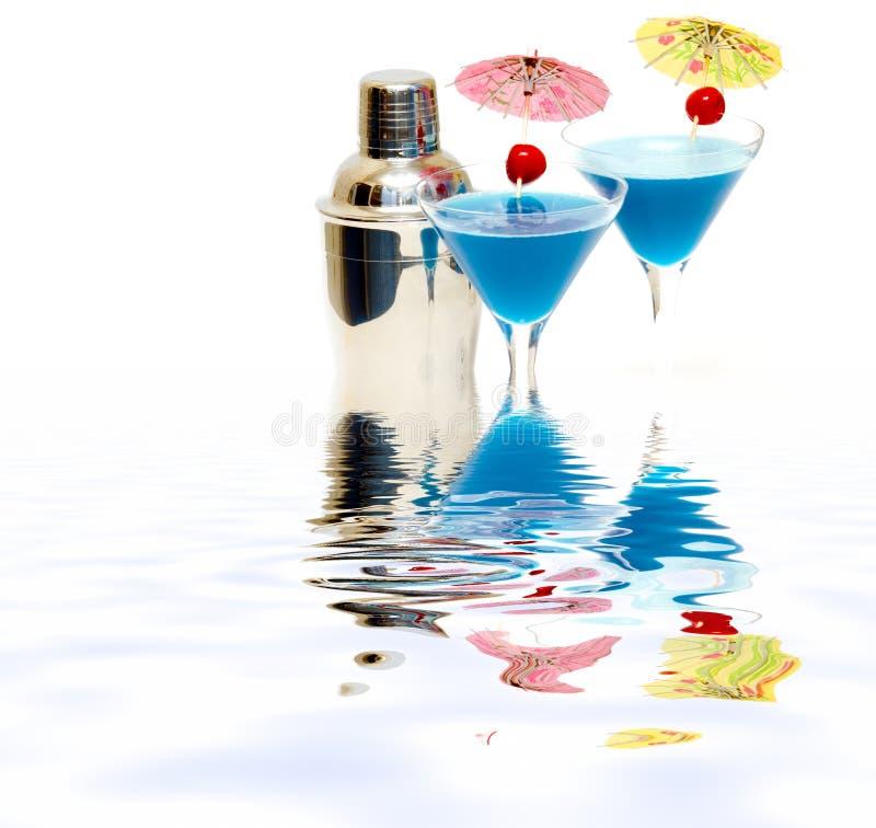 Cocktail mit blauem Curaçao u. Rüttler mit Reflexion auf Wasser lizenzfreie stockfotografie