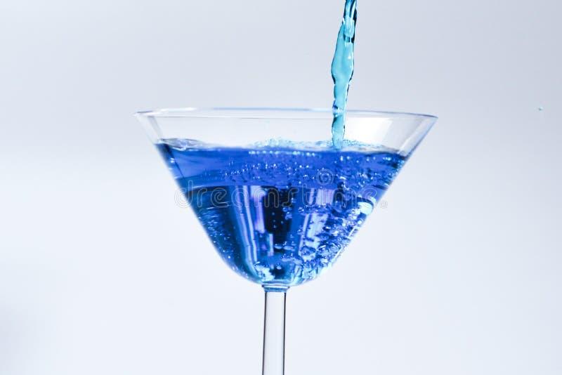 Cocktail mit blauer Fl?ssigkeit im Glas Glas mit blauem Wasser, das mit Fl?ssigkeit mit gie?t, spritzt und f?llt Martini-Glas, da stockbild