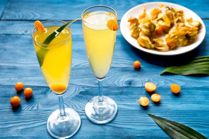 Cocktail mit Physalis im Glas auf hölzernem Hintergrund lizenzfreies stockbild