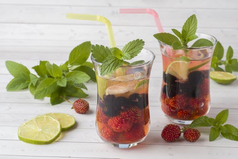 Cocktail mit Schwarzer Johannisbeere, Erdbeere, Minze und Kalk Abkühlendes Sommer-Getränk lizenzfreie stockbilder