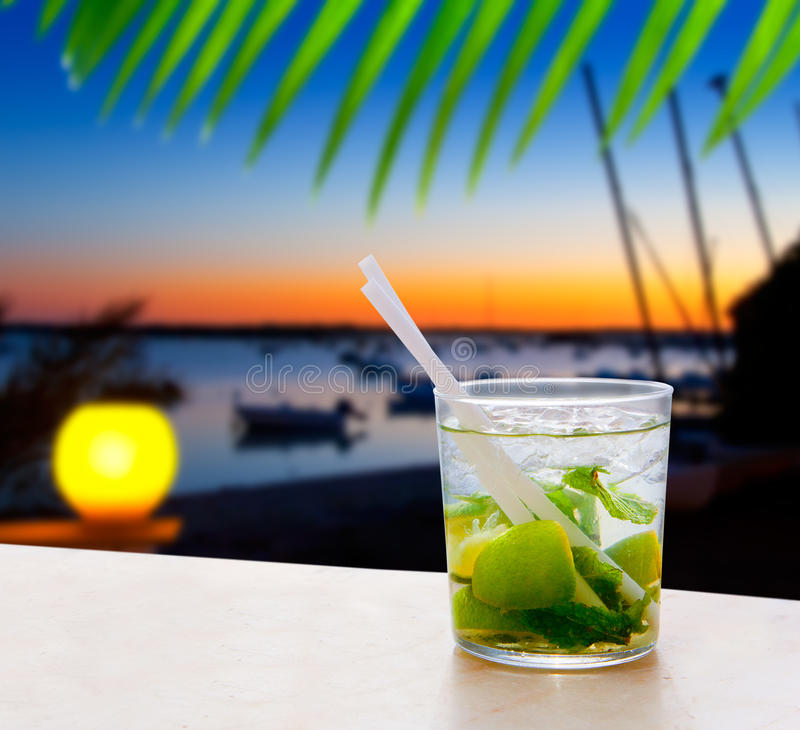 Cocktail Mojito in Balearic island sunset. And palm trees stock image