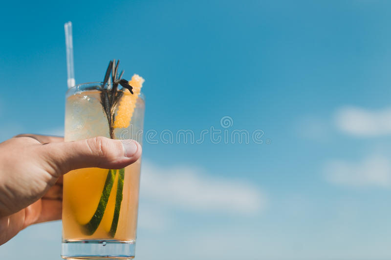 Cocktail Mojito. Glass of mojito cocktail with ice cubes and black straw on the background of blue sky stock photography