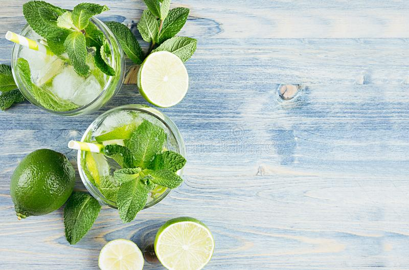 Cocktail mojito, straw and ingredients on soft shabby blue wood board, copy space, top view. royalty free stock photos