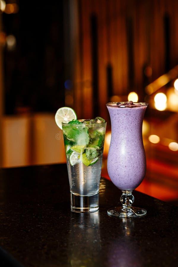 Cocktail na tabela - batido do mojito e da baga imagem de stock