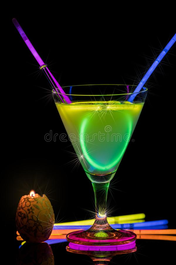 Cocktail with neon lights and candlelight. royalty free stock photo