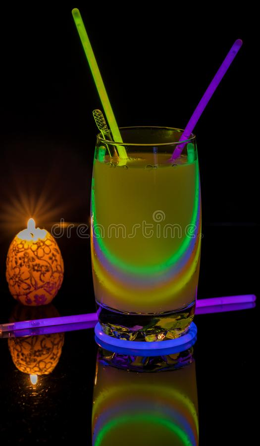 Cocktail with neon lights and candlelight. stock image
