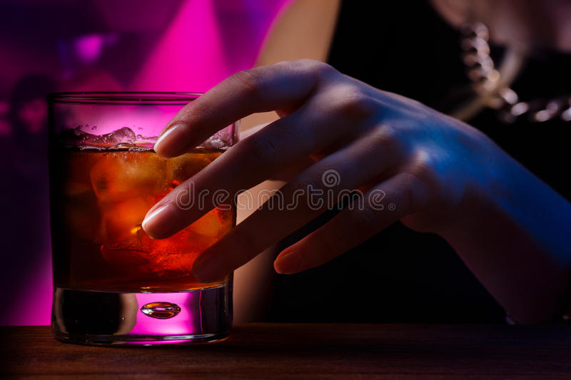 Cocktail at night club. Woman's hand holding old fashioned glass with cold cocktail against blurred night club background royalty free stock photography