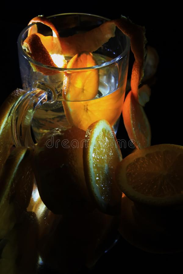 At night, a little sun in a glass of orange tea or juice. Cocktail night reunion or acquaintances a little orange juice or just pieces of fruit can date an royalty free stock image