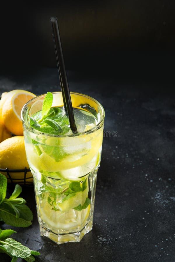 Cocktail o limonata di Mojito con calce e la menta in vetro di highball sulla tavola nera Fine in su Bevanda di estate immagine stock libera da diritti