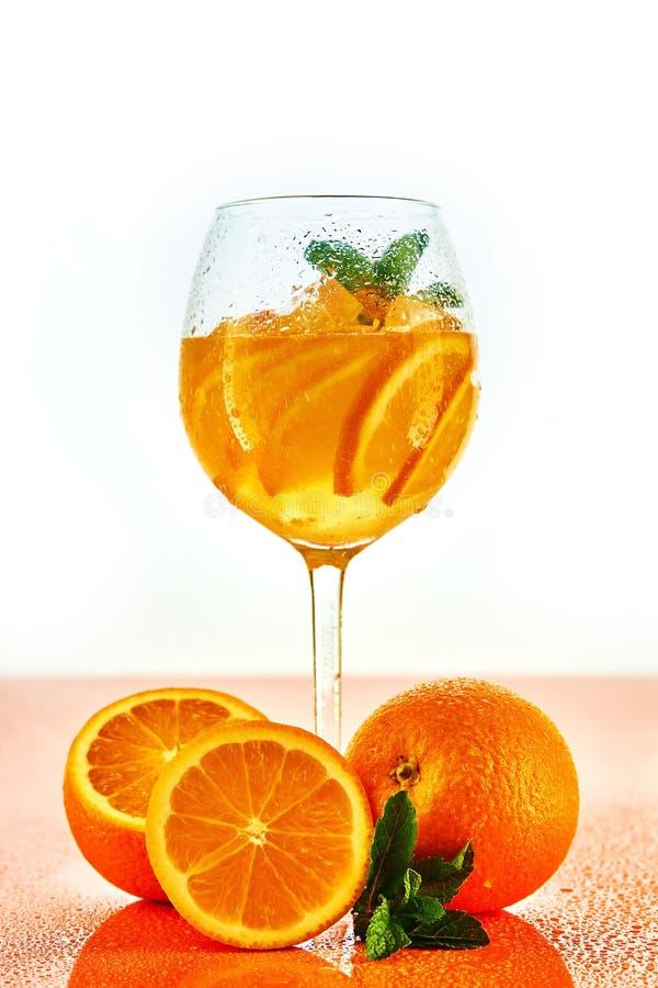 cocktail orange en verre de vin avec la menthe sur le fond blanc avec des oranges photo stock