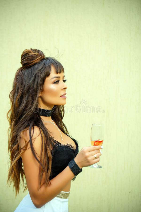 Cocktail party or holiday celebration. Girl holding glass of wine on beige wall. Drinking alcohol concept. Woman with long brunette hair in black lace bustier royalty free stock photography