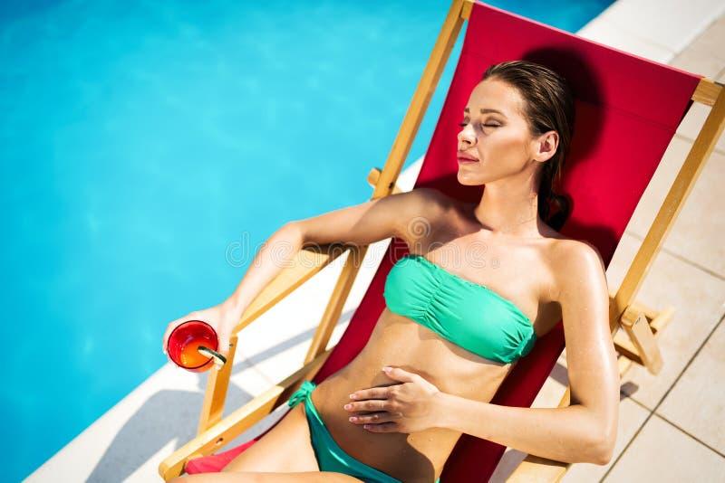 Cocktail potable de belle femme et prendre un bain de soleil ? la piscine photo libre de droits