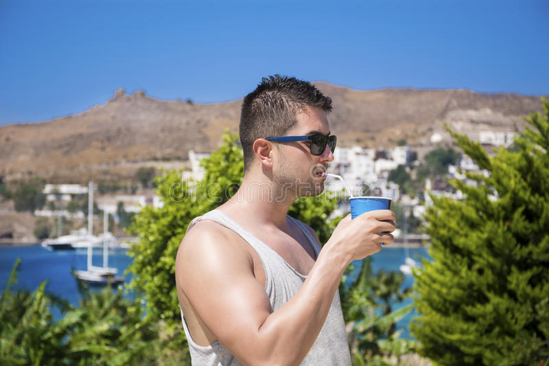 Cocktail potable de jeune bel homme dans un jardin tropical image stock