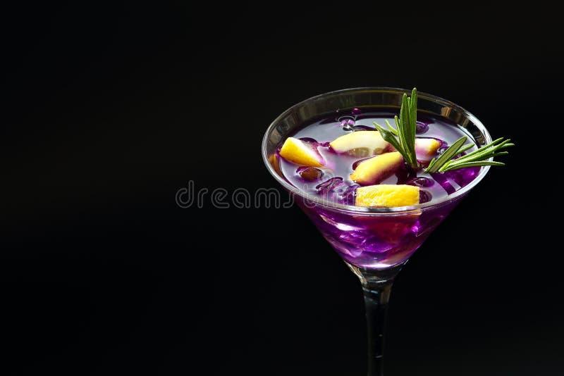 Cocktail pourpre de pluie d'été frais dans un verre de martini avec des tranches de citron sur une surface texturisée noire photo stock