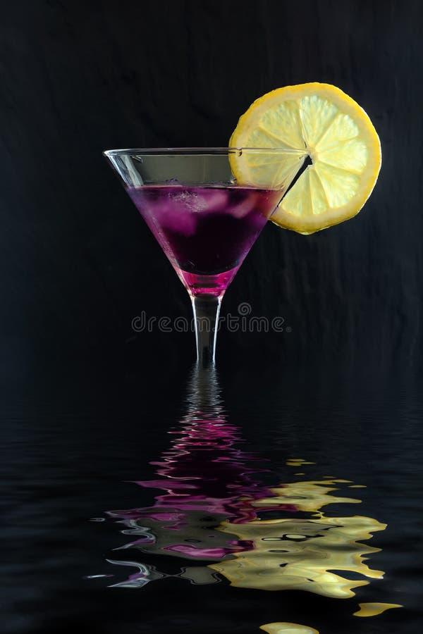 Cocktail pourpre frais de pluie dans un verre de martini avec la tranche de glace et de citron sur une surface texturisée noire, photos stock