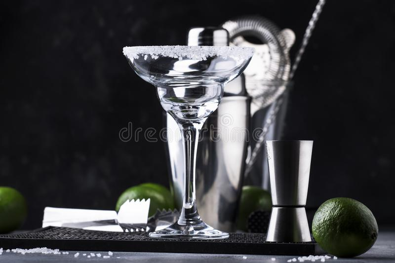 Cocktail preparation concept. Empty margarita cocktail glass, shaker and bar tools, lime and salt on dark bar counter stock image