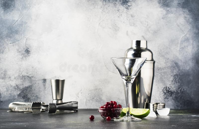 Cocktail preparation scene with bar tools and ingredients, gray bar counter background, copy space stock images