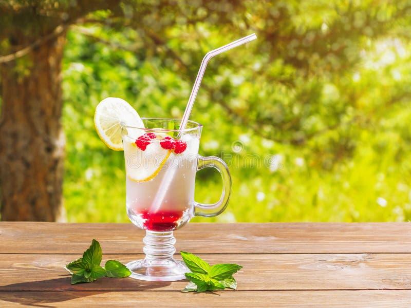 Cocktail régénérateur d'été avec le citron, la framboise et la menthe une table en bois photographie stock libre de droits