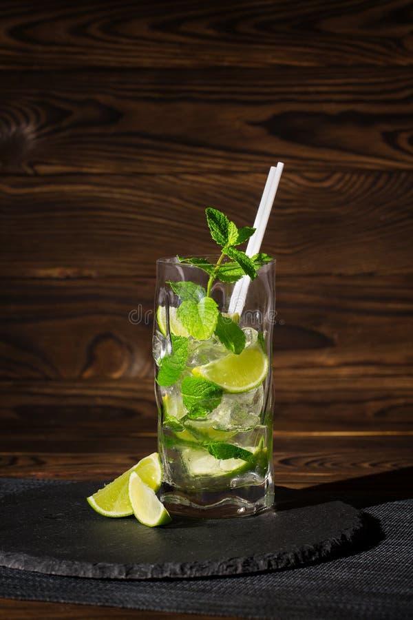 Cocktail régénérateur de mojito avec la menthe, les glaçons et les tranches de chaux dans un verre de highball sur le fond en boi images stock